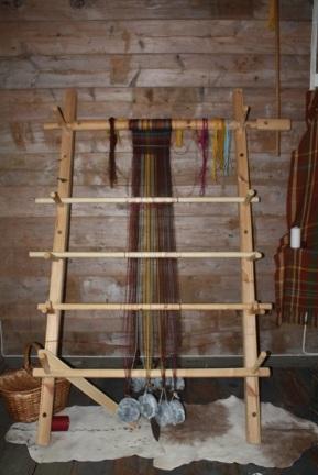Oppstadveven min består av en tøybom på toppen, to sidestolper, 3 vevskaft og en skillestokk i bunn sammen med vektsteiner av kleberstein